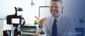 a businessman smiling at the camera, shooting a webinar
